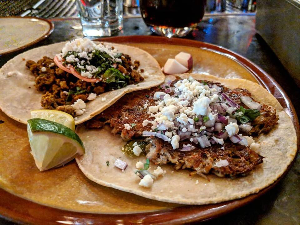 Two shredded beef tacos and a wedge of lime sit on a plate at Lone Star Taco Bar in Cambridge