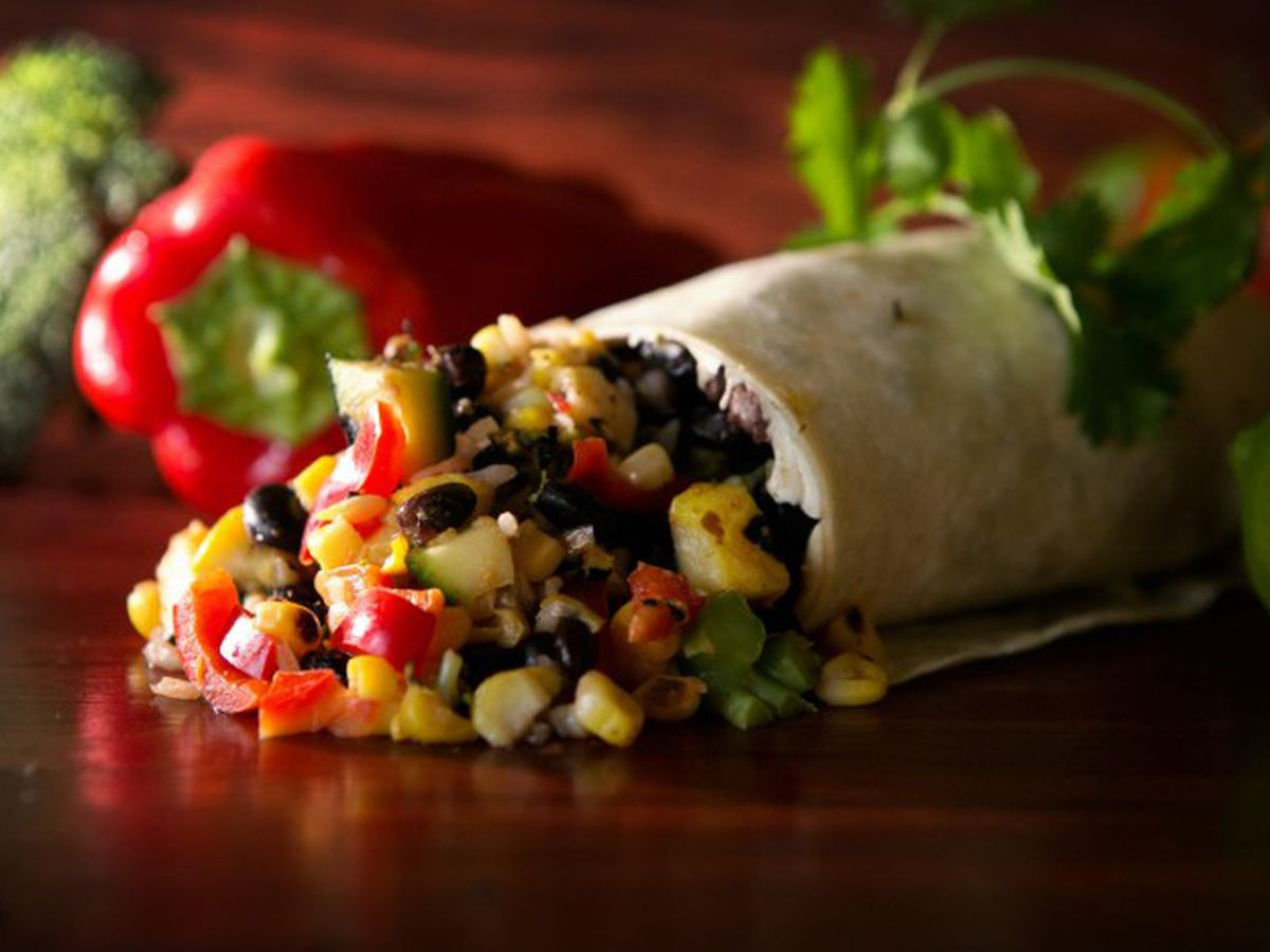 Corn, black beans, and red pepper pieces spill out of burrito on a dark wood surface. A red pepper and cilantro sit in the background.