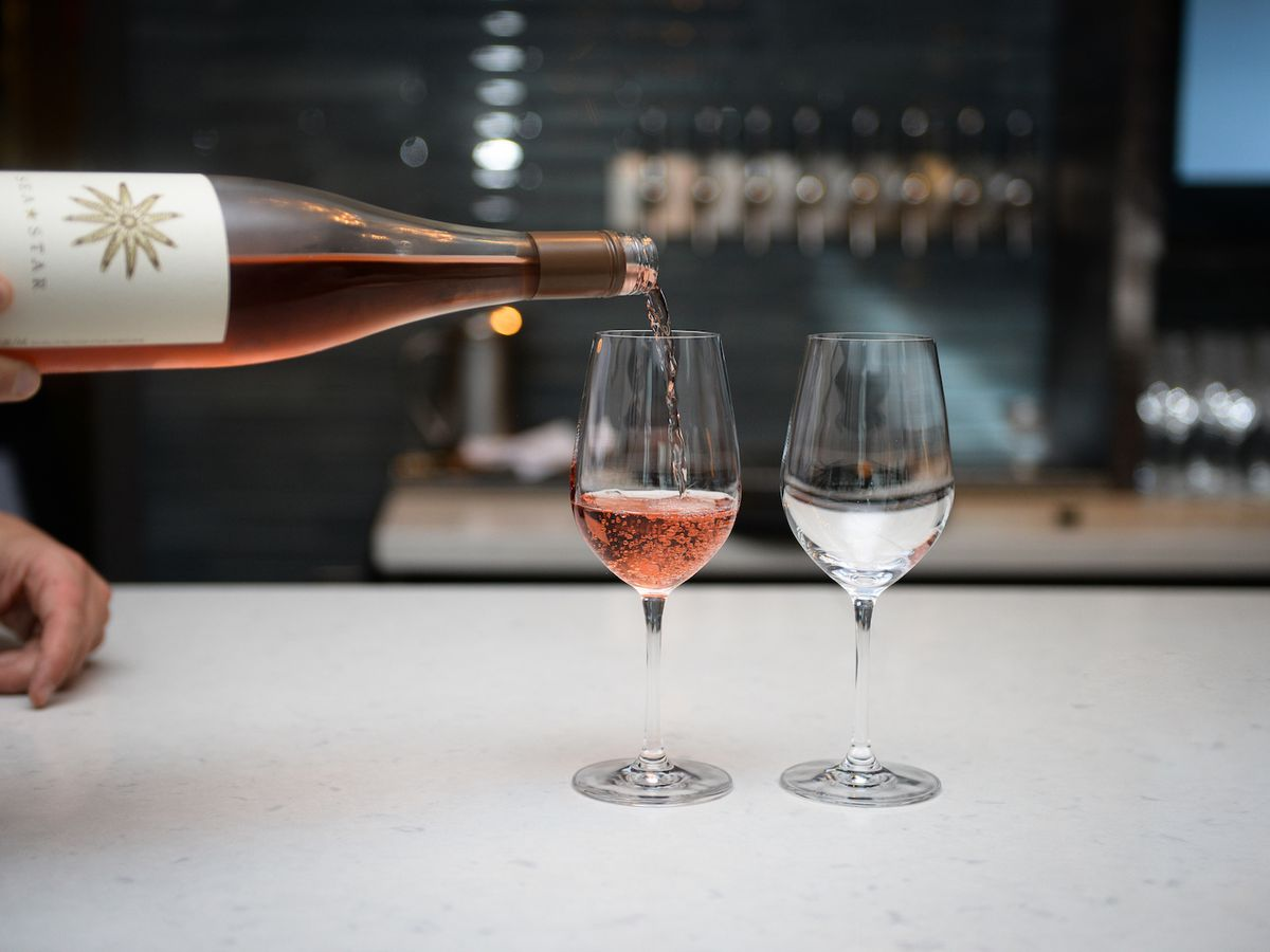An unseen server pours a bubbly rose into one of two wine glasses sitting on a bright white counter