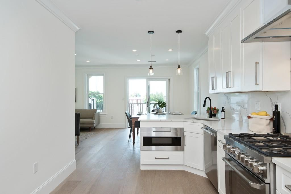 The view of a kitchen that leads into a living room, and everything's sleek and new-looking.