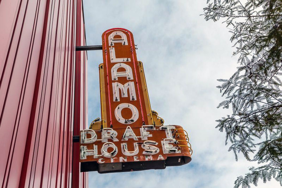 neon theater sign with blade that says Alamo Drafthouse