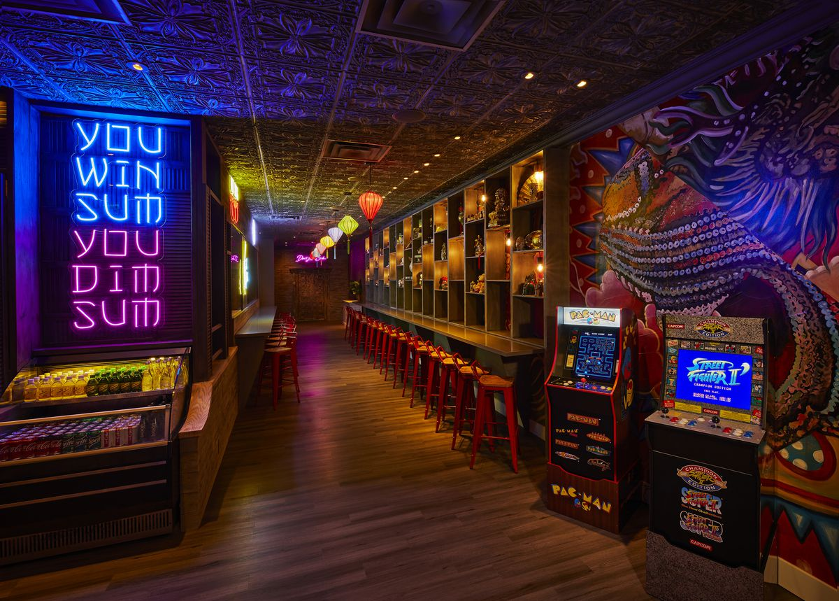 dark room with chairs and video games on the right and neon sign on the left
