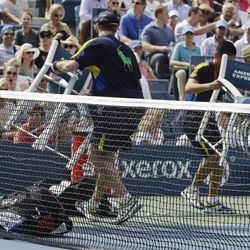 Ball persons return chairs and tennis gear to the sidelines after a gust of wind blew them onto the court during a semifinal match between Britain's Andy Murray and Tomas Berdych, of the Czech Republic, at the 2012 US Open tennis tournament,  Saturday, Sept. 8, 2012, in New York.