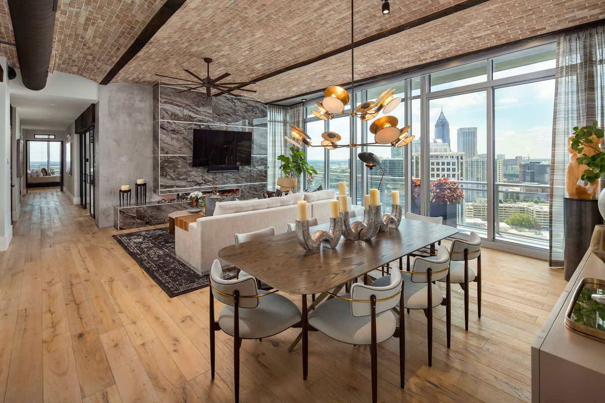 A living room with a large dark ceiling fan and penthouse views across Midtown Atlanta.