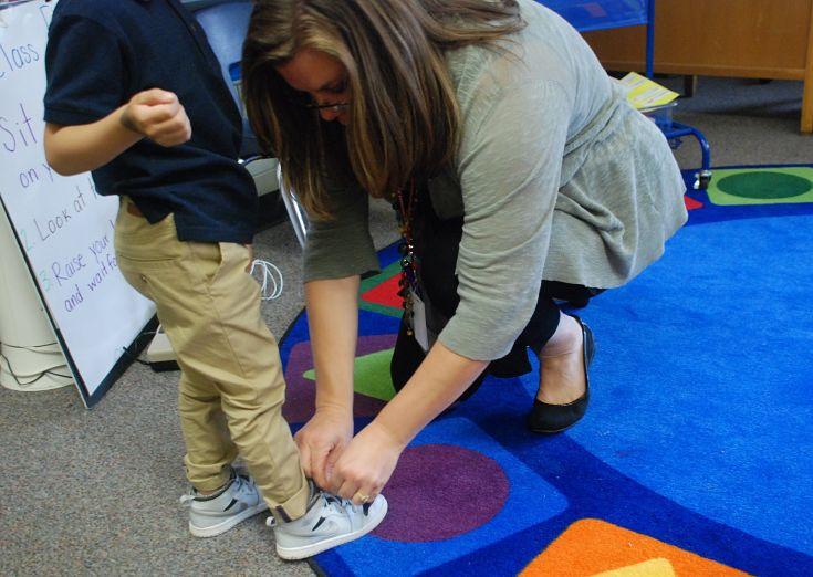 Brandy Barhite ties a child's shoe. (Photo by Melanie Asmar)