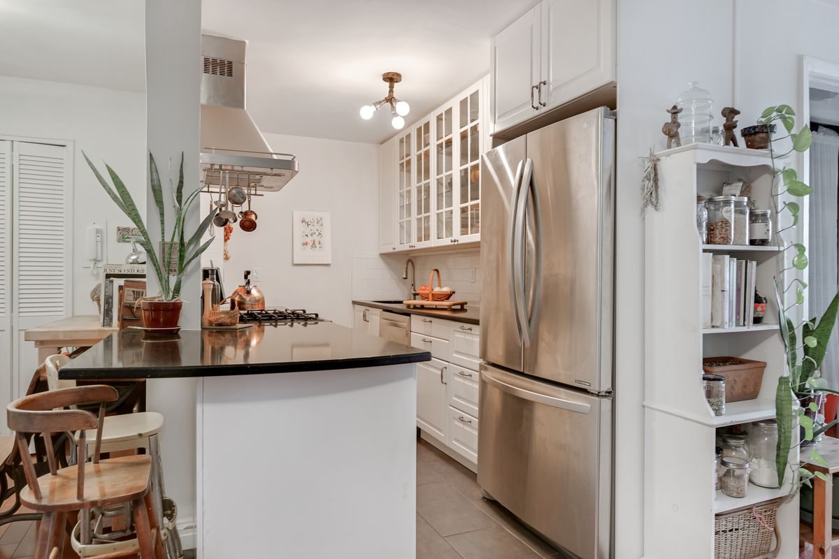 A kitchen with a large island and white cabinetry.