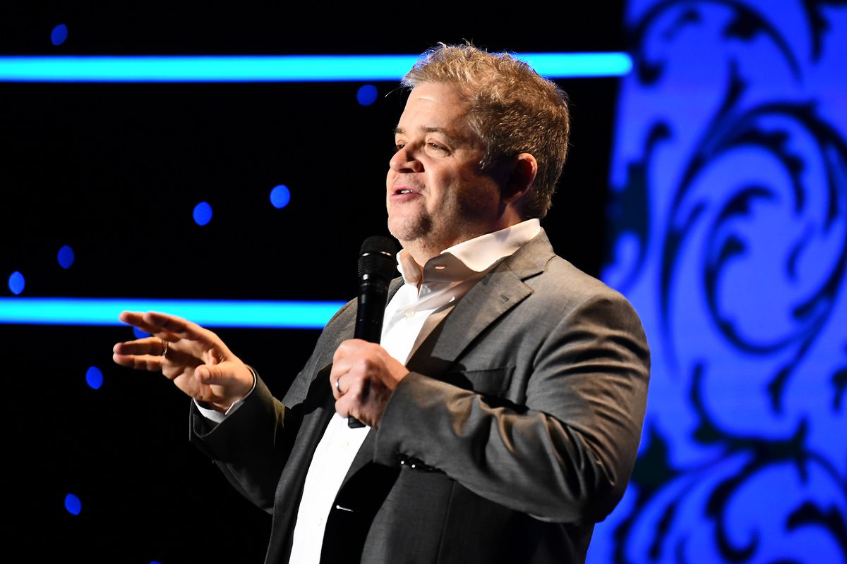 Comedian Patton Oswalt, wearing a white shirt and grey blazer, holds a mic in front of a black backdrop featuring teal and bright blue graphics.