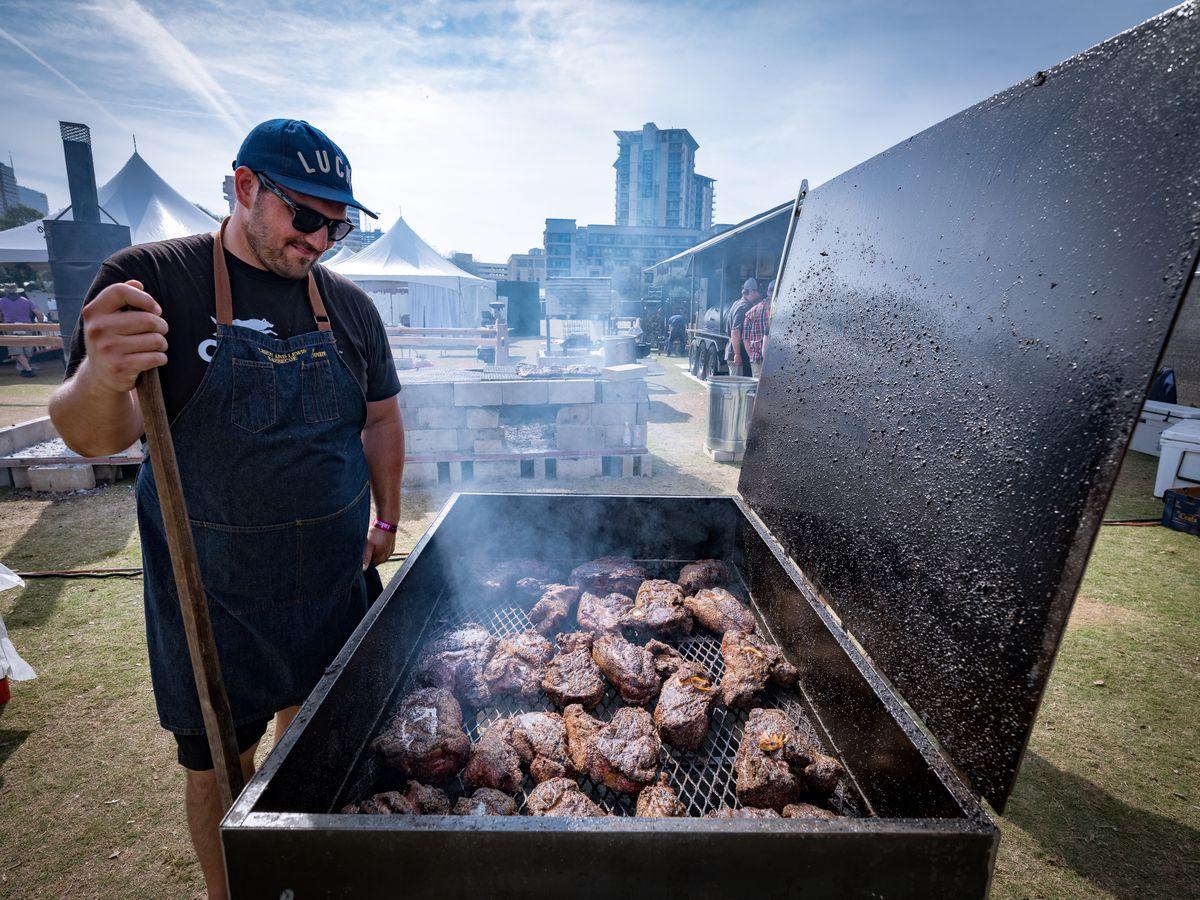Evan LeRoy checking on his pork steaks