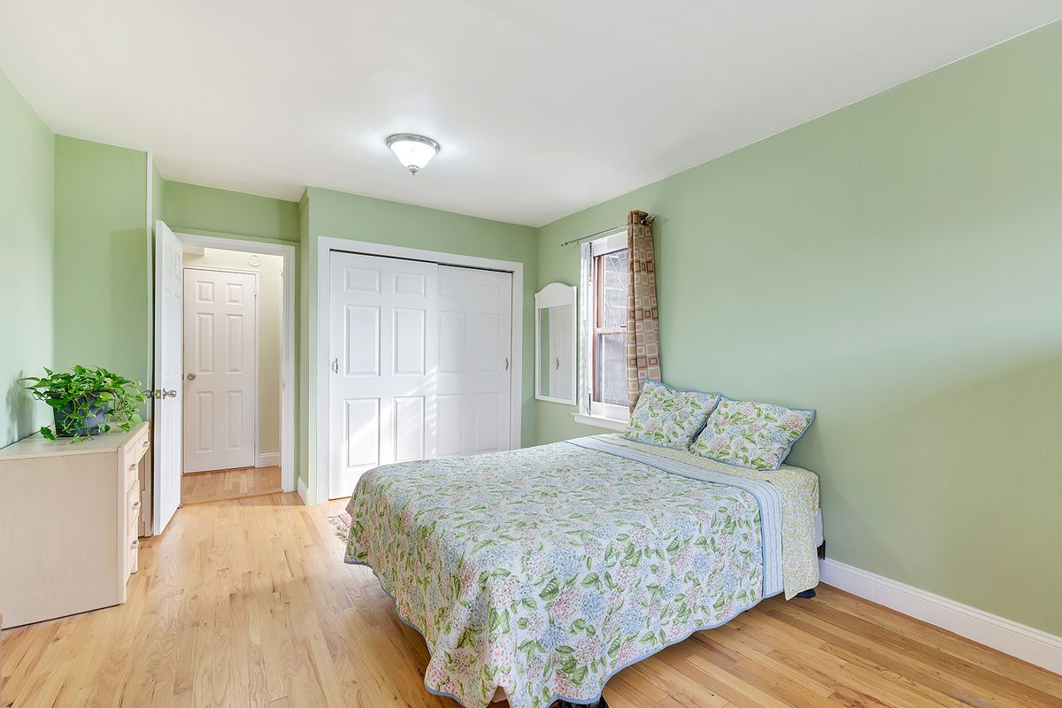 A bedroom with green walls, a medium-sized bed, and hardwood floors.