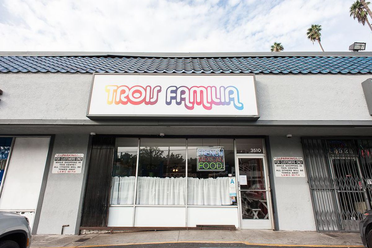 Outside of the former Trois Familia, with the sign showing against a cloudy sky.