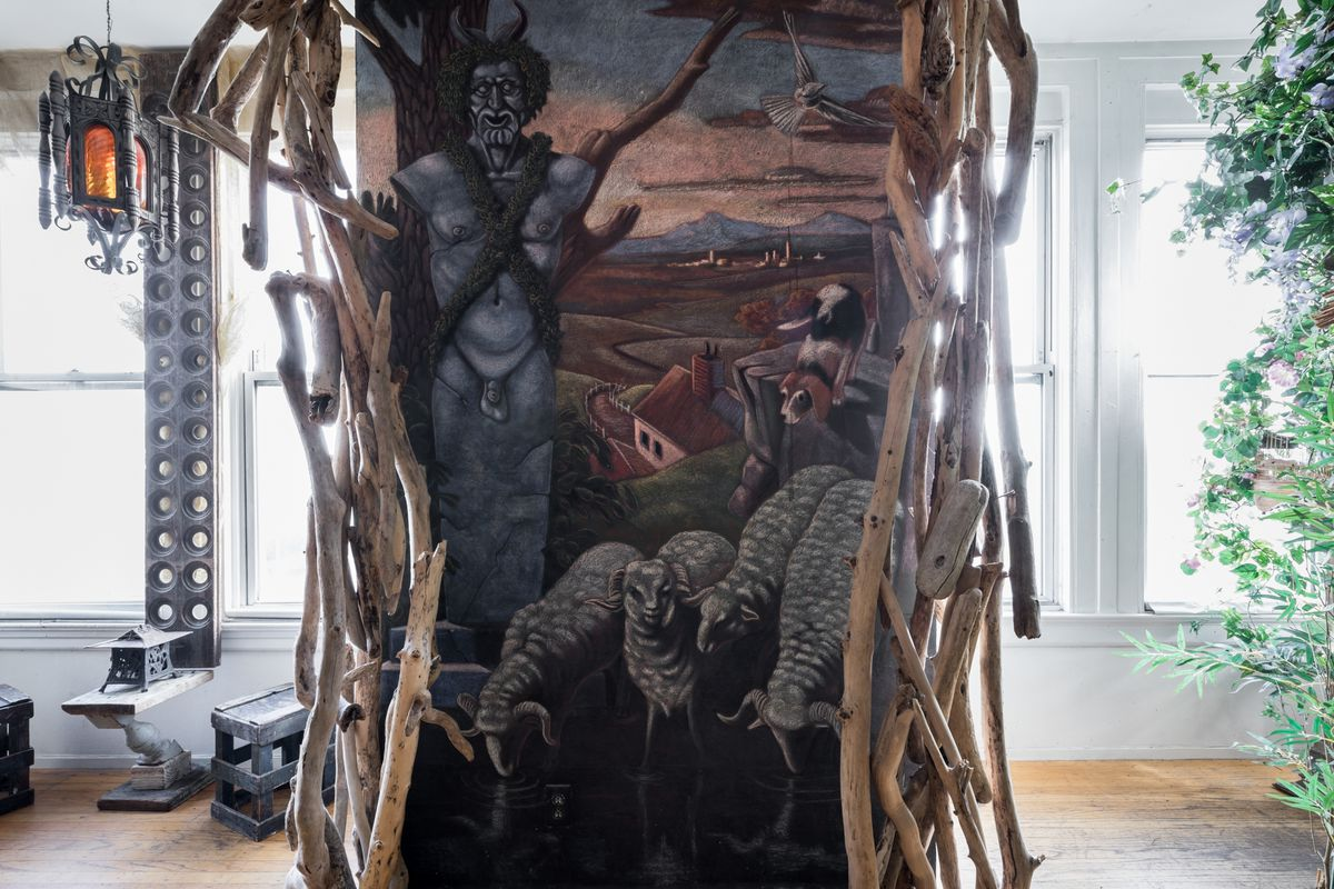 A large mural and work of art sits in a wooden structure in a room that has multiple windows letting in natural light. There is a plant in a planter next to the wall.