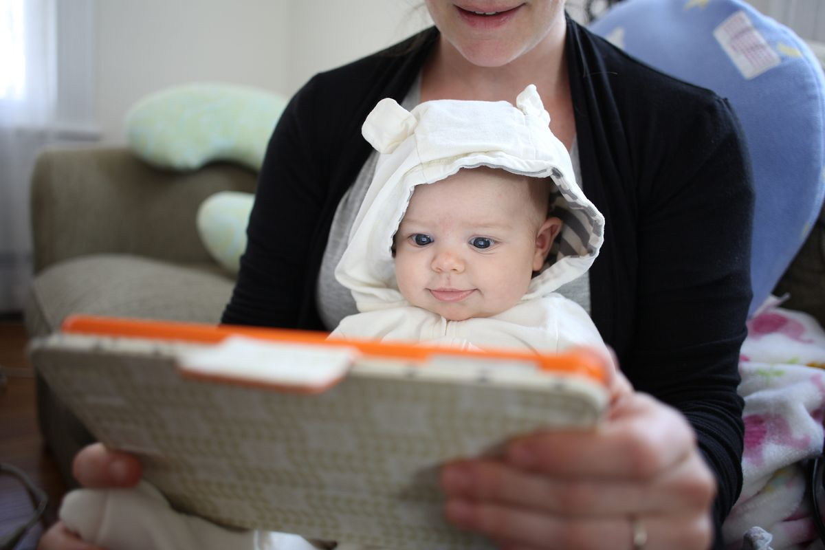 A baby smiles while looking at a tablet computer.