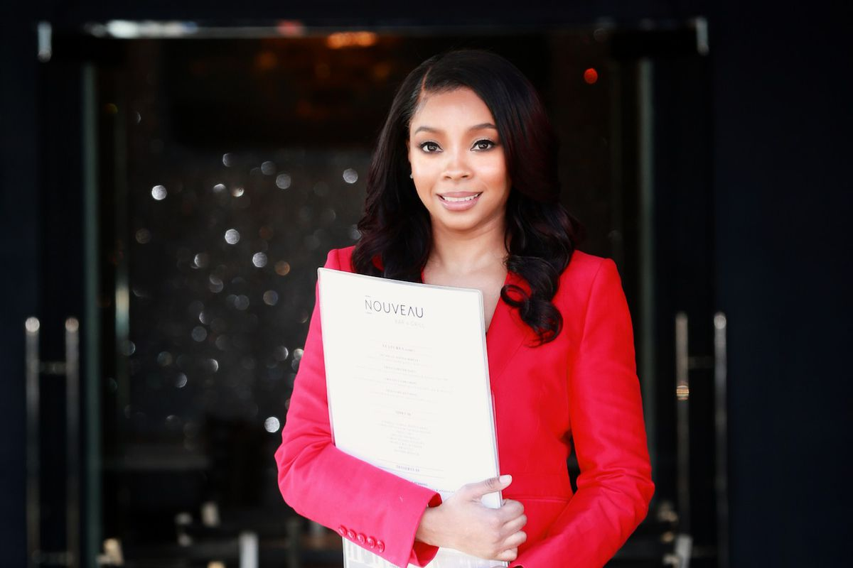 Nouveau Bar and Grill owner Ebony Austin wearing a hot pink blazer and black leather leggings holding a large menu from the restaurant. Austin stands in front of the dining room at her College Park restaurant location in front of a four-top table with the chandelier hanging the background