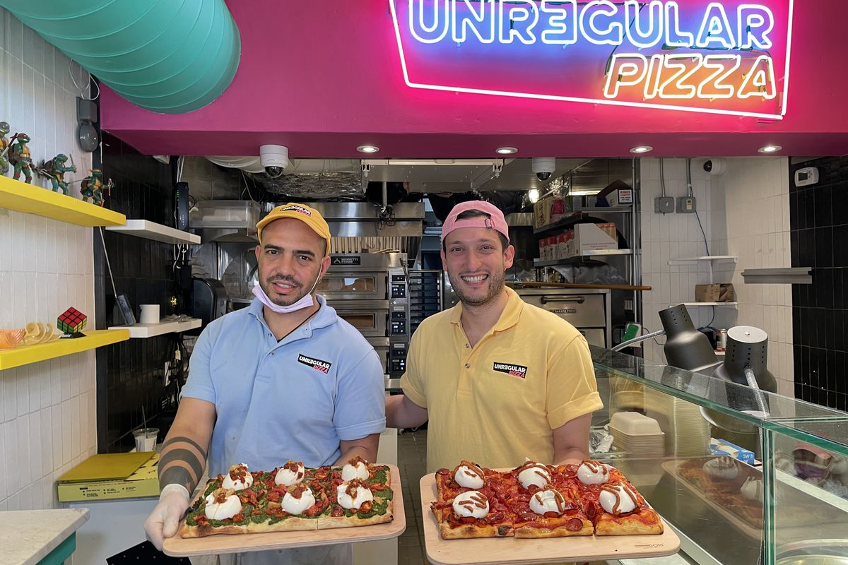 Two people holding pizzas on wooden boards smile at the camera while standing in a newly-opened pizza shop