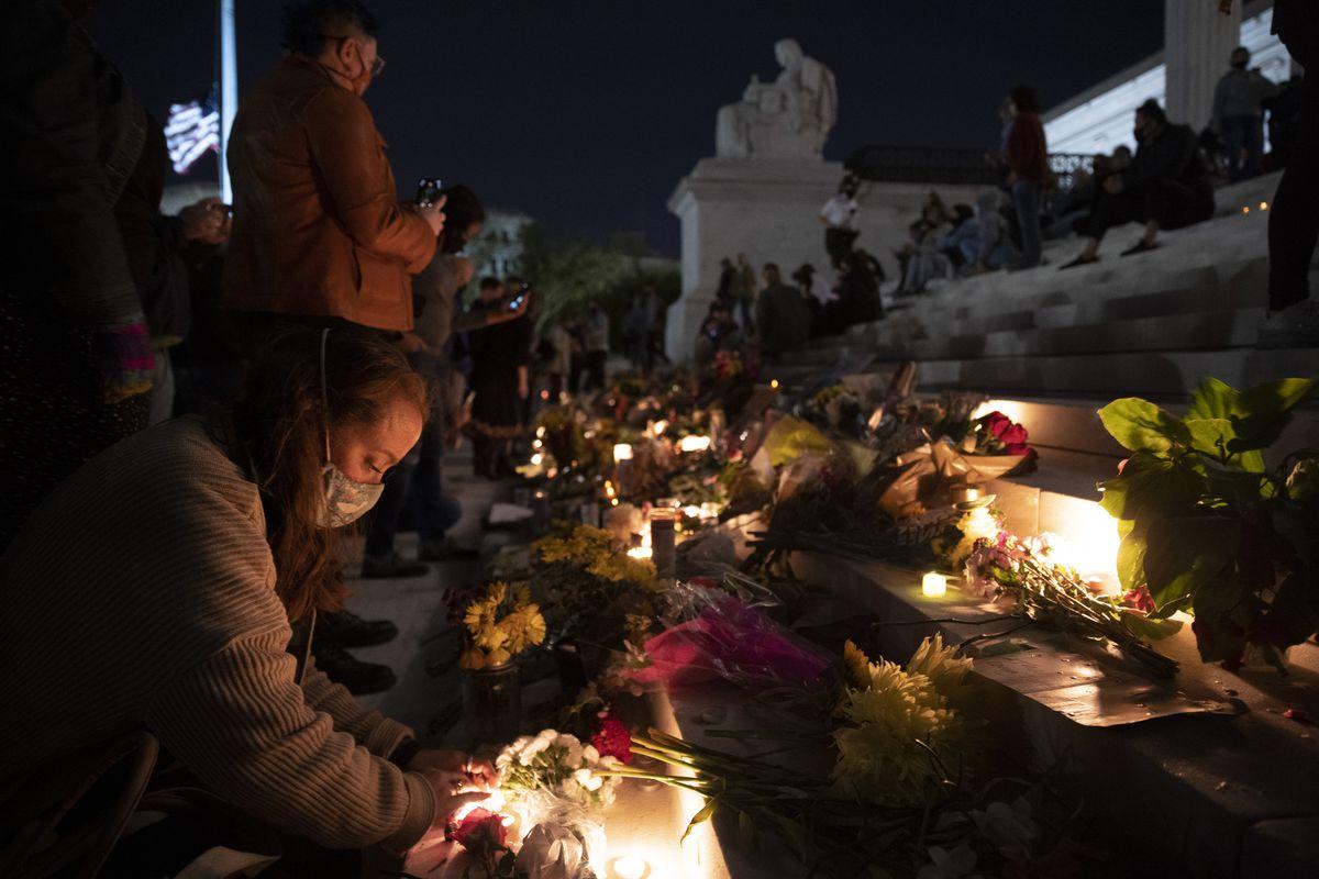 Một người phụ nữ đeo mặt nạ đặt hoa trên các bậc thềm của Tòa án Tối cao, nơi được bao phủ bởi những bó hoa.  Cô ấy và những người đưa tang bên cạnh cô ấy được thắp sáng bởi những ngọn nến đã được đặt giữa những bông hoa.