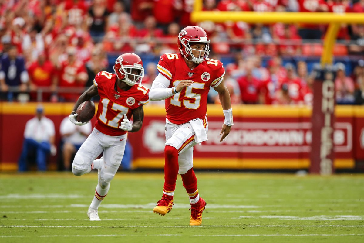 Patrick Mahomes of the Kansas City Chiefs runs ahead looking for a block for Mecole Hardman of the Kansas City Chiefs at Arrowhead Stadium in the second quarter against the Baltimore Ravens on September 22, 2019 in Kansas City, Missouri.
