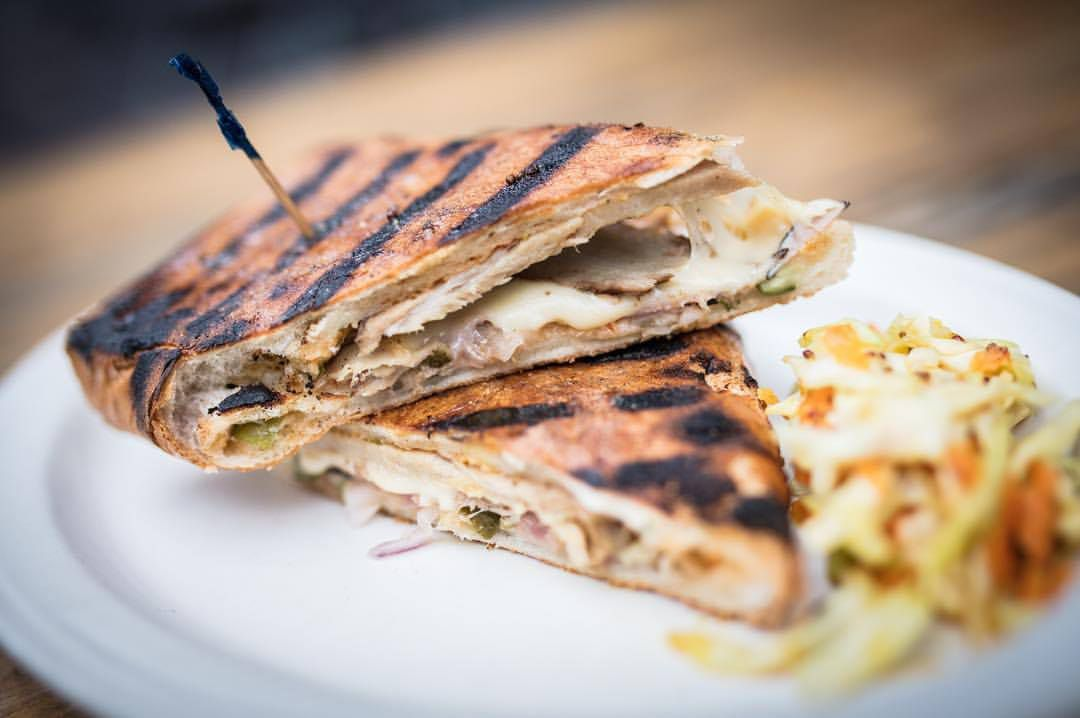 A Cubano sandwich , stuffed with pork and grilled, served on a white plate on a wooden table