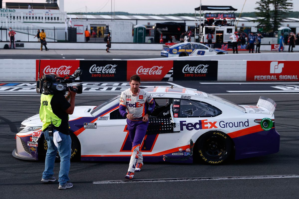 Denny Hamlin, driver of the #11 FedEx Ground Toyota, exits his car after winning the NASCAR Cup Series Pocono 350 at Pocono Raceway on June 28, 2020 in Long Pond, Pennsylvania