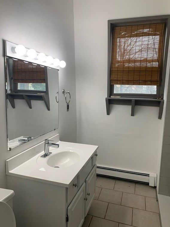 A small bathroom with a small sink and a single window.