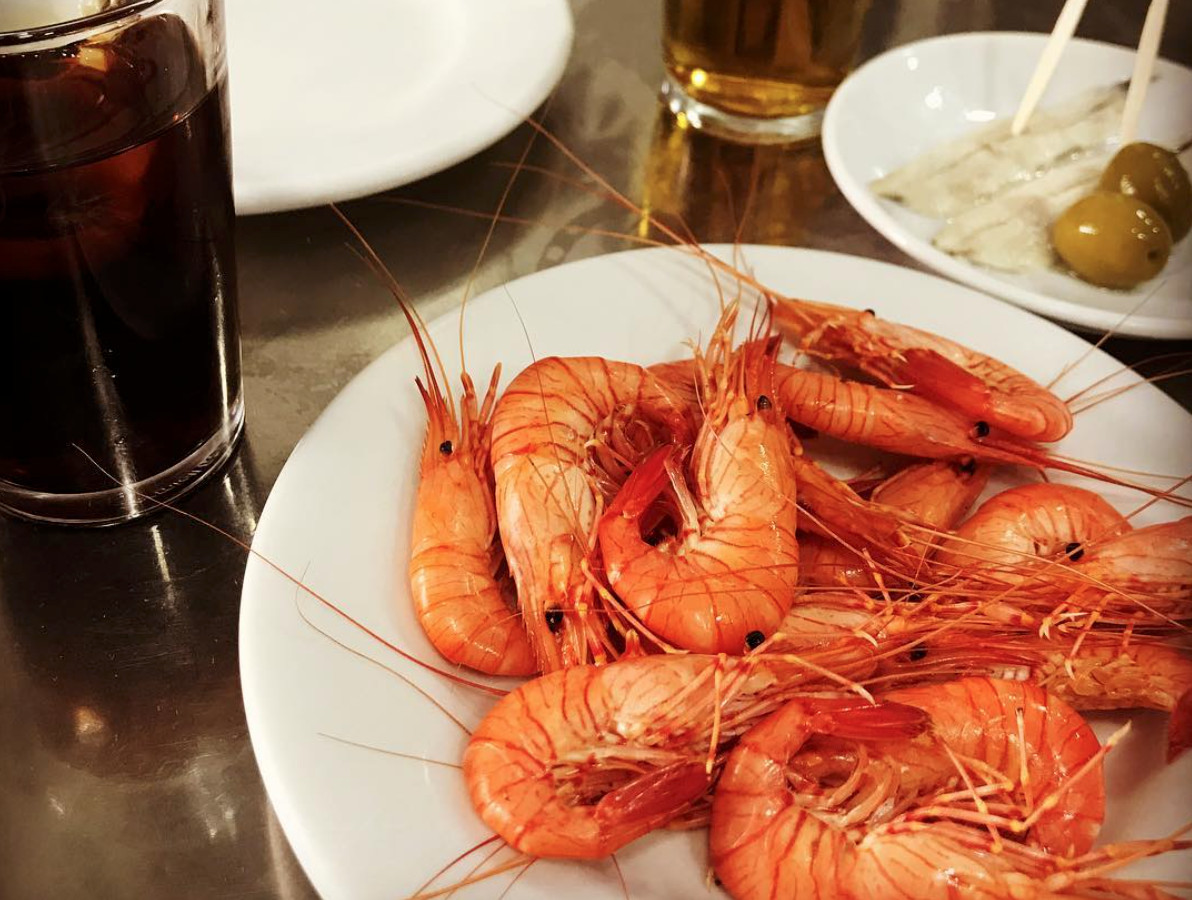 A plate full of many head-on shrimp beside a glass of vermouth with soda and a nearly empty plate of olives.