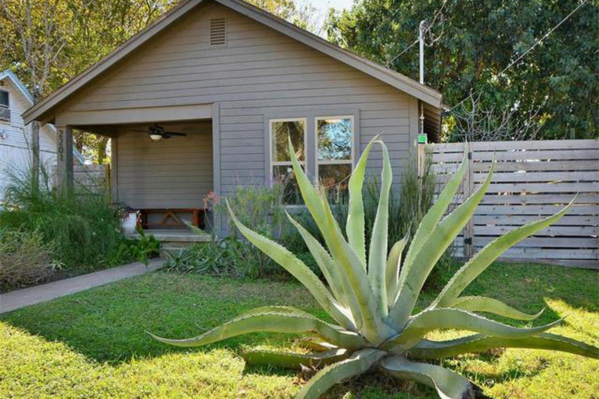 Small gray wooden bungalow with big agave in front