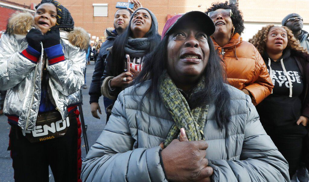 Cahana Yehudah, foreground, of the Bronx, cries as she hears the response of prisoners held inside the Metropolitan Detention Center, a federal facility with all security levels, Sunday, Feb. 3, 2019, in the Brooklyn borough of New York. The prison has be
