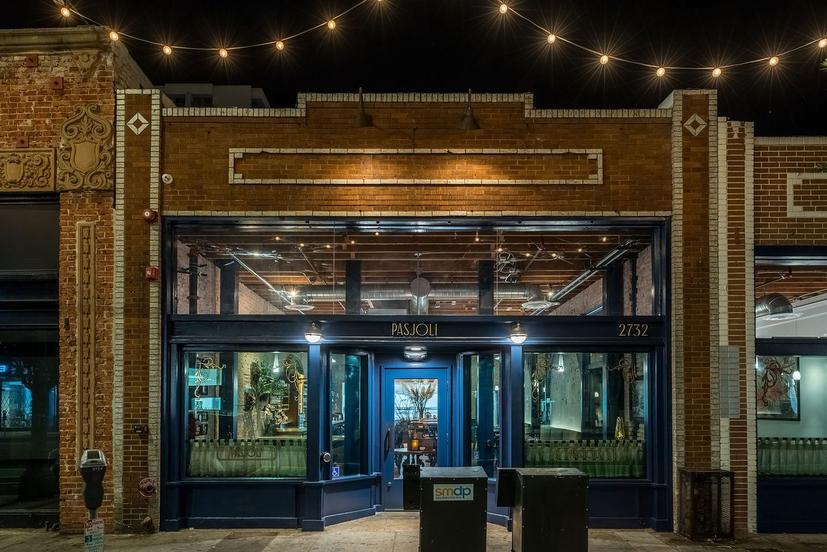 A brick building with a French bistro inside, bathed in dark light and deep blue tones.