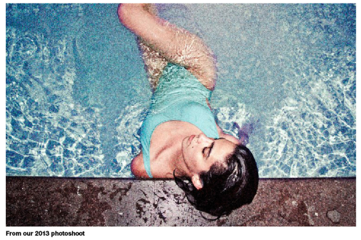 A woman reclines in a pool wearing a turquoise one piece bathing suit.