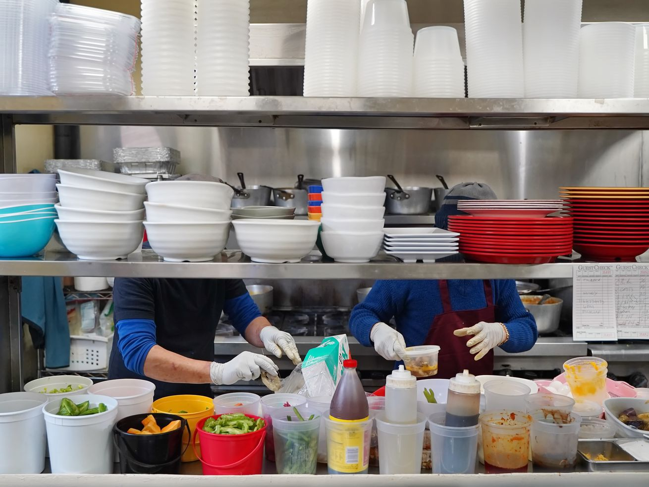 Two cooks wearing gloves in the kitchen