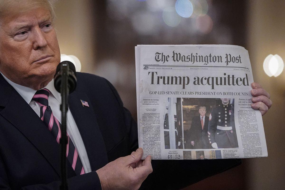 "President Donald Trump holds up a copy of the Washington Post with the headline ""Trump acquitted."""