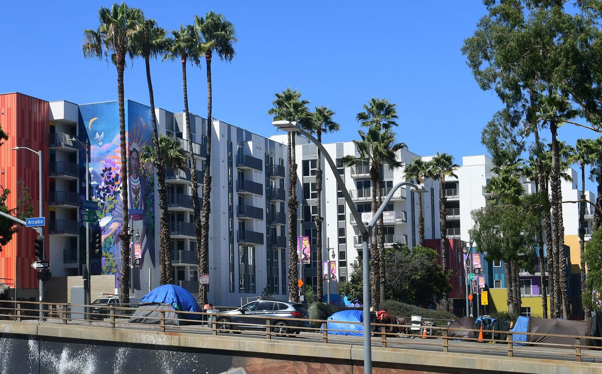 Tents belonging to homeless people are seen by new highrise developments alongside a freway ramp in Los Angeles.