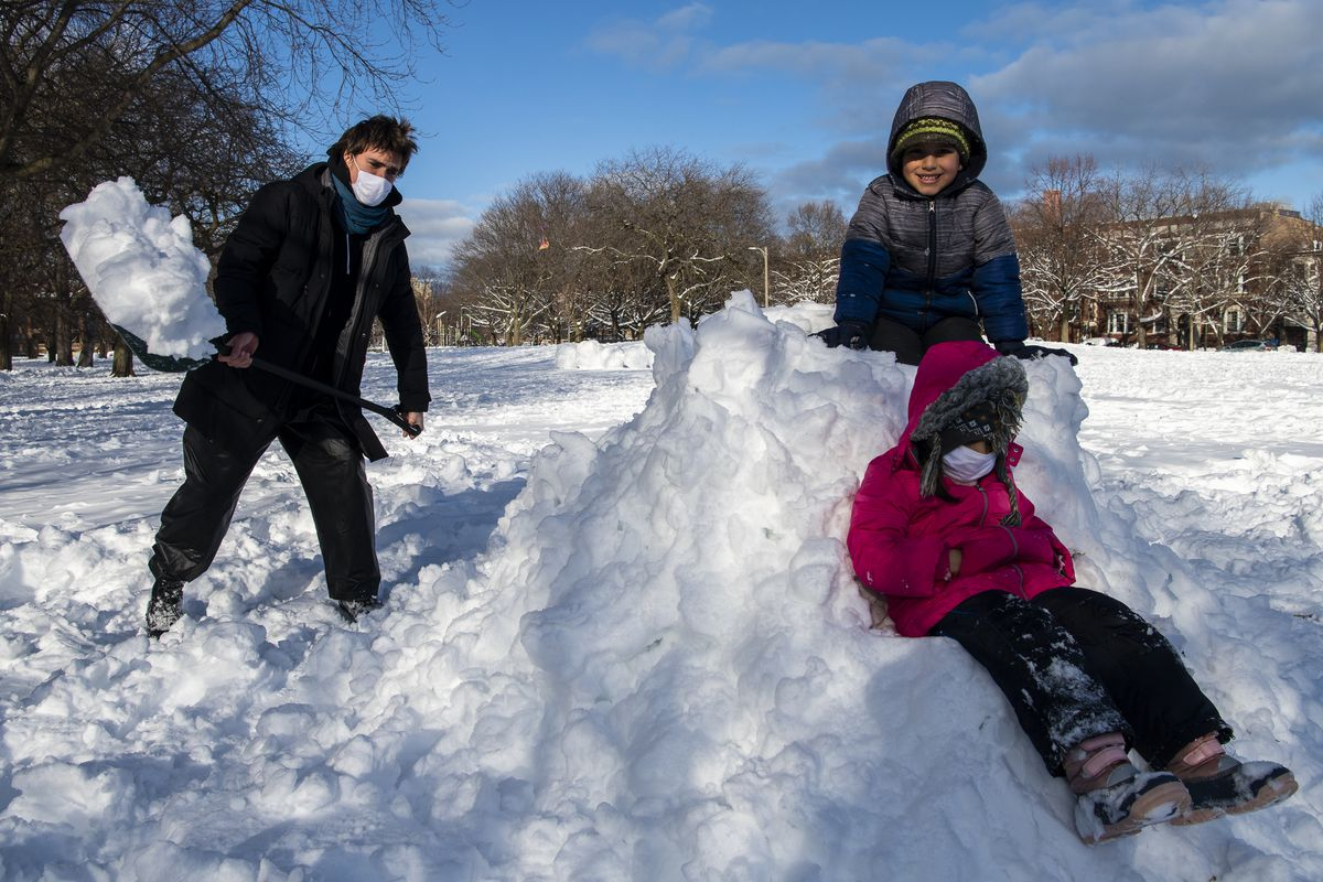 Sawyer French shoves snow into a pile to create a snow fort for Sina, grey, and Ava, pink, Doostar at Nichols Park in the Hyde Park neighborhood
