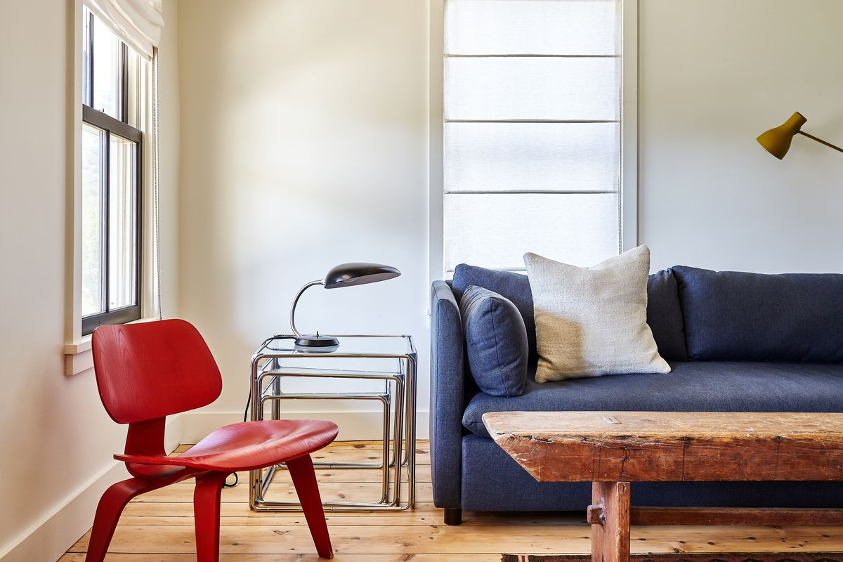 A red Eames LCW chair sits next to the blue sofa and antique bench-turned-coffee-table.