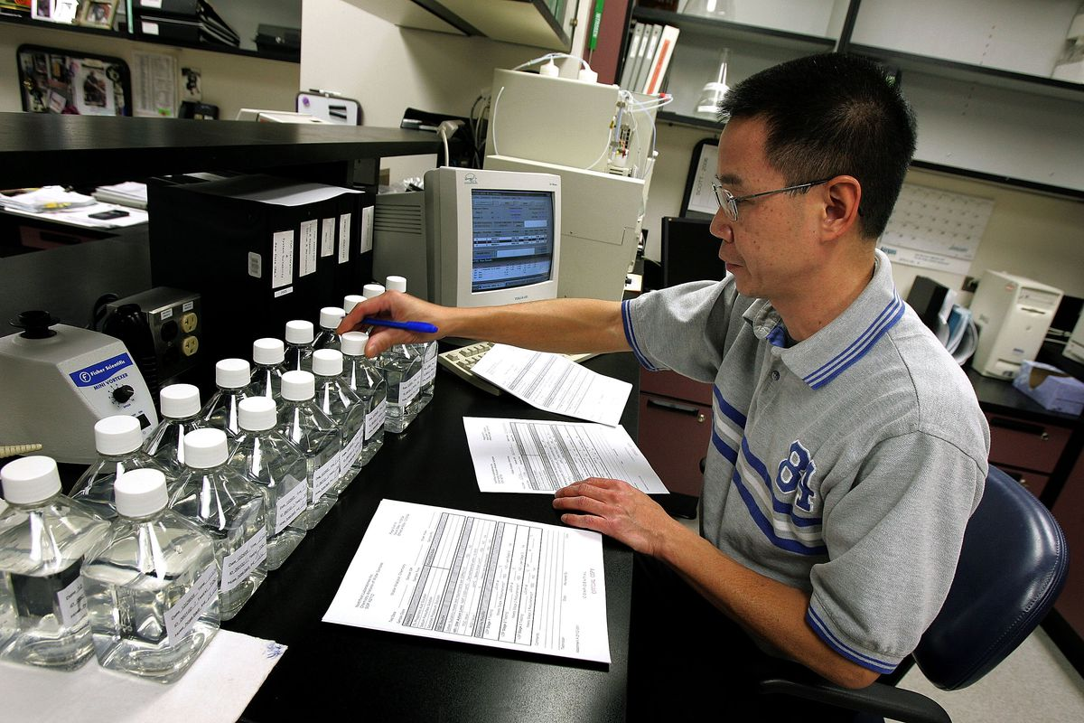 A technician sits at a lab bench in order to test bottle of blood substitute.