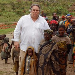 In this December 2007 photo obtained by The Associated Press, the Rev. Carl Keyes stands for a photo with impoverished people of the Batwa Tribe in Burundi during a delivery of relief supplies to the area. Keyes accompanied an established aid group to look into program possibilities, and after this trip, he created Aid for the World. (AP Photo)