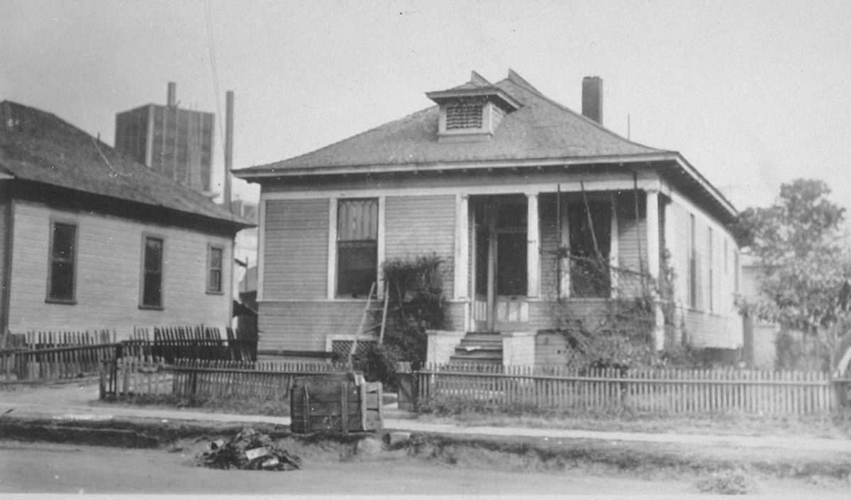 An old black and white photo of a humble home enclosed behind  a simple wood fence. The home has a small front porch, wood siding, and a pitched roof.