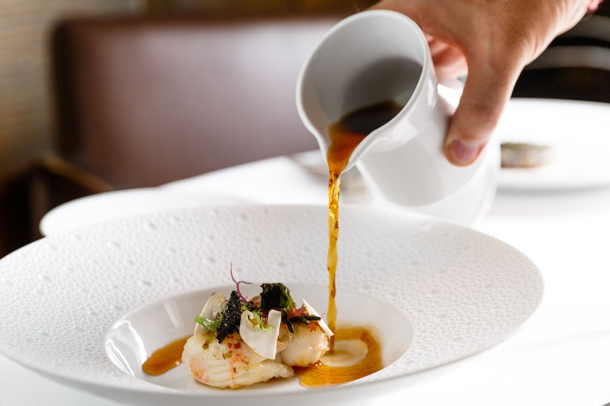 A waiter pours a dark dashi broth into a bowl of langoustines with matsutake mushrooms and seaweed