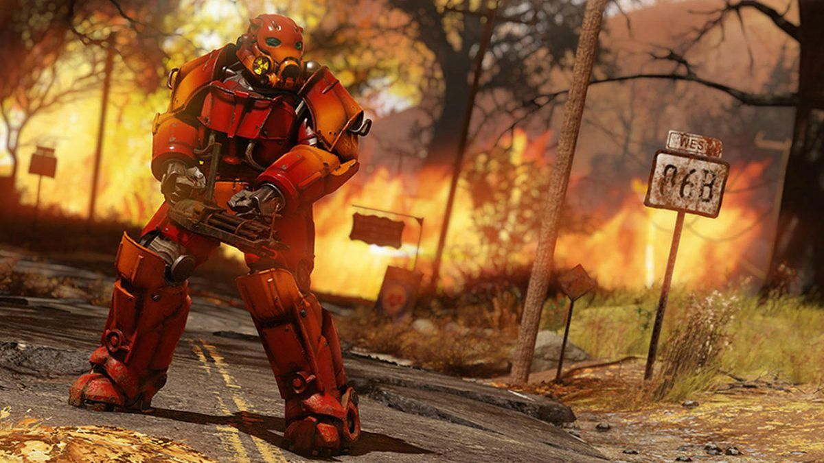 A fighter in a hulking set of red Power Armor readies a minigun against a background blazing with fire.