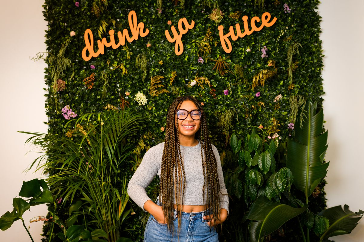 """Smith-McCarthy stands in front of a wall of plants and flowers at Drink Mamey, with the words """"drink ya juice"""" hanging above her"""