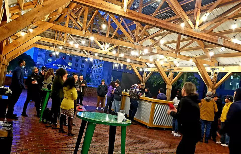 People in fall clothing stand under a lit wooden structure that is set up as a pop-up outdoor beer garden.