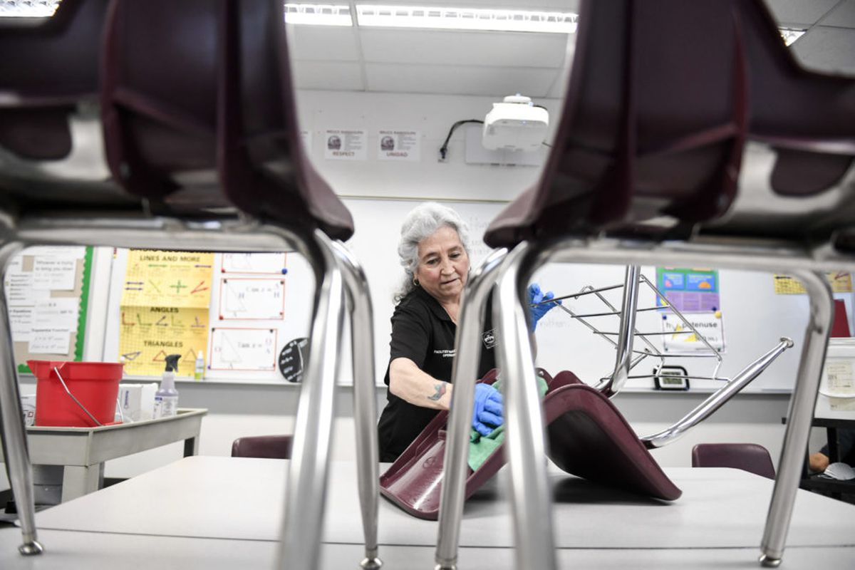 Lenora Vallejos cleans chairs at Bruce Randolph School in Denver on Thursday, March 19, 2020.