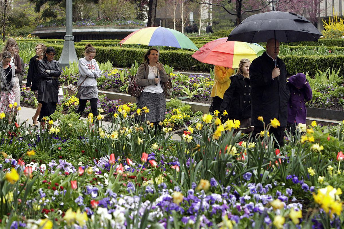LDS conference attendees walk past the flowers on Temple Square.