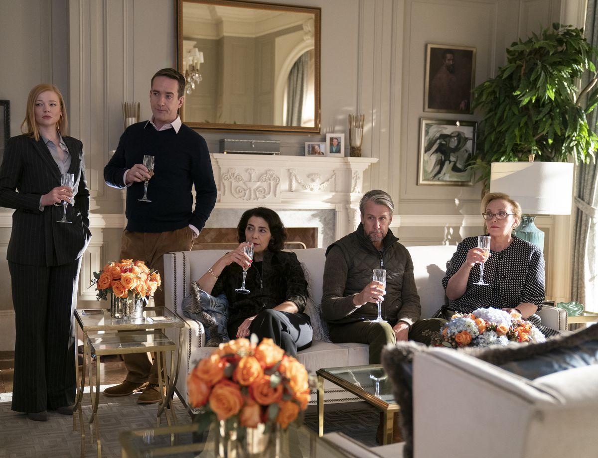 Shiv (Sarah Snook), Tom (Matthew Macfadyen), Marcia (Abbass), Connor (Alan Ruck), and Gerri (J. Smith-Cameron all hold glasses of champagne.