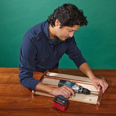 Man Secures Base Fittings Of Copper Log Holder