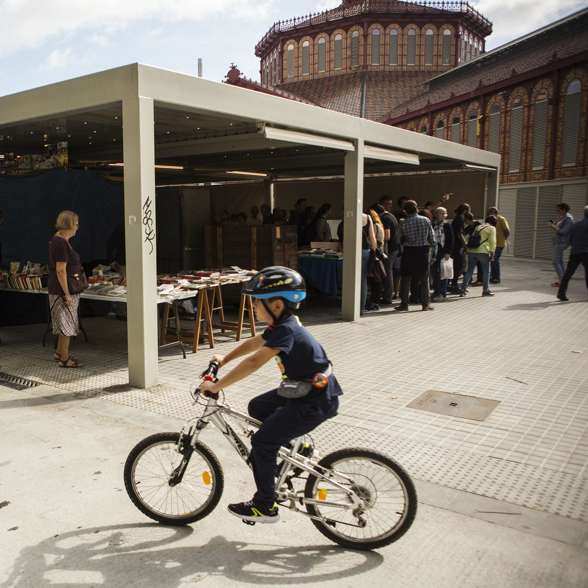 A boy rides a bike next to the open-air book market outside the newly renovated Sant Antoni market, in a superblock.