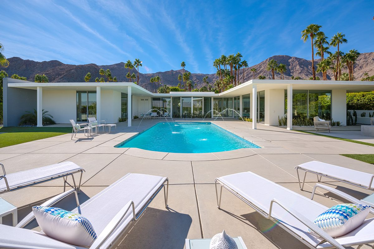 Exterior shot of back of the house looking toward it from the pool. White house configured in H-shape with flat overhanging roof with mountain and palm trees in the vista.