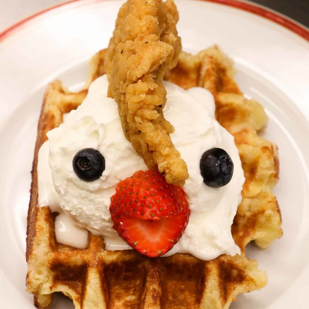 """The sweet and savory """"Waffle Monster"""" prepared with chicken tenders, a strawberry beak and a  Belgium waffle and whipped cream."""