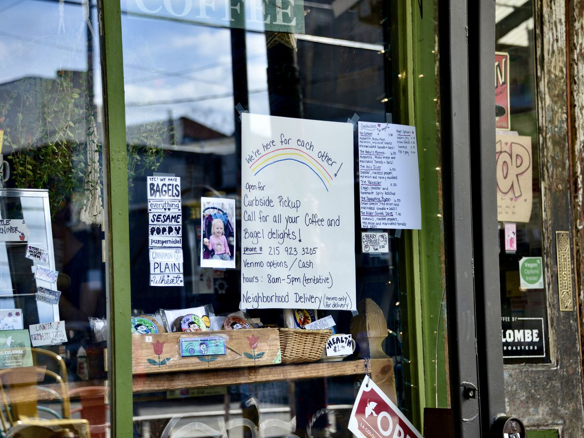 coffee shop storefront with handwritten sign outlining ordering policies