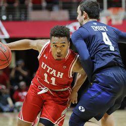 Utah Utes guard Brandon Taylor (11) draws a foul on Brigham Young Cougars guard Nick Emery (4) as Utah and BYU play in the Huntsman Center in Salt Lake City Wednesday, Dec. 2, 2015. Utah won 83-75.