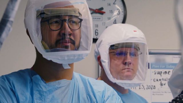 Two medical professionals in PPE in Totally Under Control